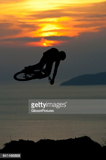 A young man does a full rotation off a big jump on his mountain bike at sunset.