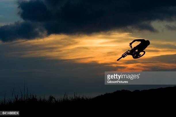 Un jeune homme fait une rotation complète sur un grand saut sur son vélo de montagne à la fin de la journée.