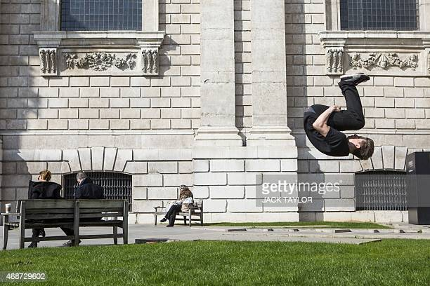 A young man does a somersault outside St Paul's Cathedral in central London on April 6 2015 as England basks in higher than expected temperatures on...