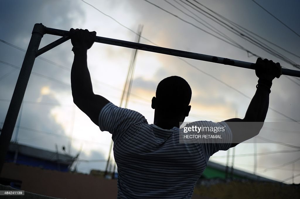 A young man does pull-ups in a gym in the Jalousie neighborhood of Petionville, a suburb of Port-au-Prince on April 11, 2014. AFP PHOTO/Hector RETAMAL
