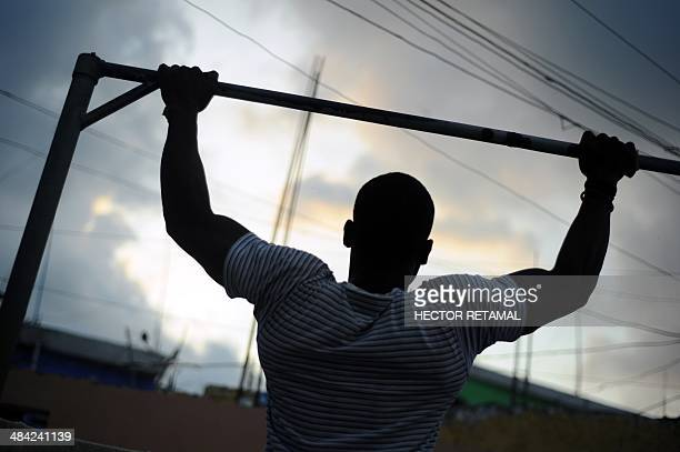 A young man does pullups in a gym in the Jalousie neighborhood of Petionville a suburb of PortauPrince on April 11 2014 AFP PHOTO/Hector RETAMAL