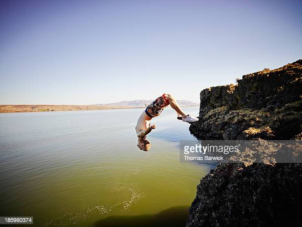 Young man doing a backflip off cliff into river