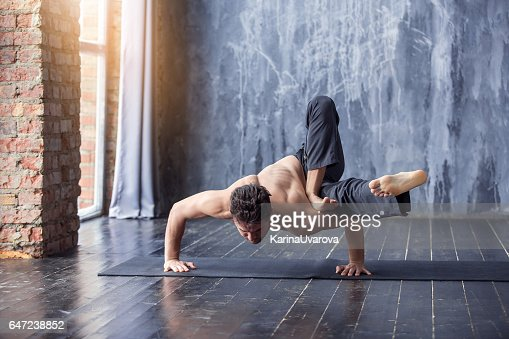 Young man doing an asana ashtavakrasana : Stock Photo