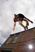 Young man doing back flip from wall, outdoors, low angle view