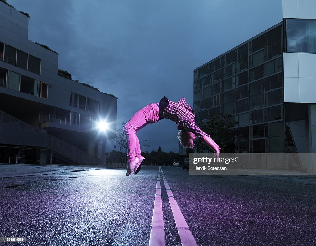young man doing back flip in the street : Stock Photo