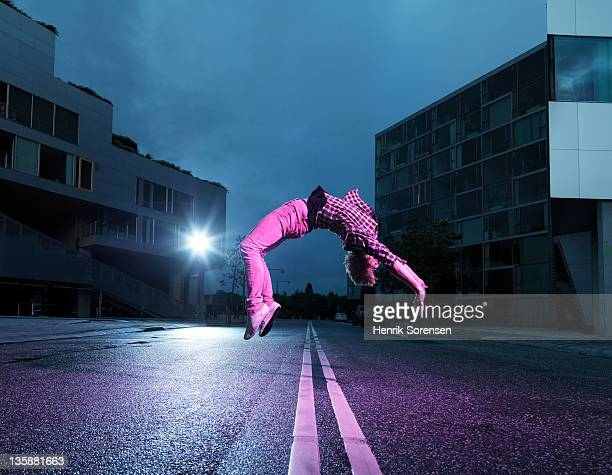 young man doing back flip in the street