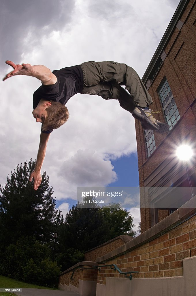 Young man doing back flip off wall, outdoors