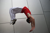Young man doing backflip, mid air, blurred motion