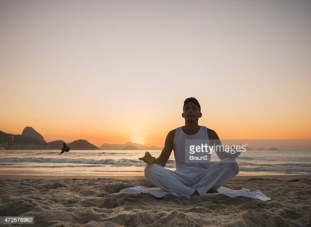 Young man doing breathing exercises on the beach at sunset.