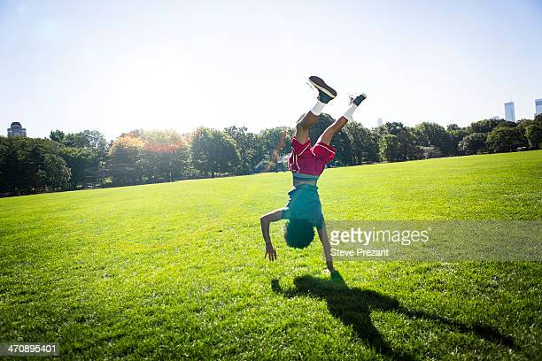 Young man doing cartwheel in park
