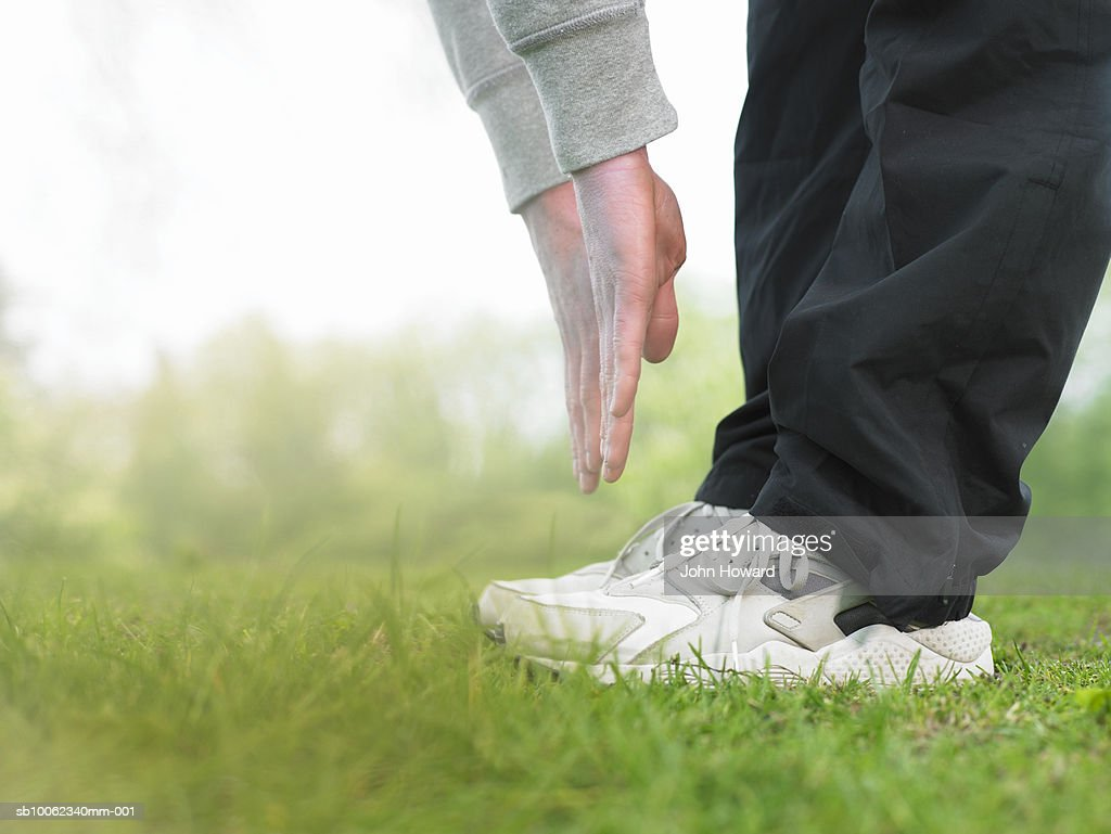 Young man doing exercises on grass, low section : Stock Photo