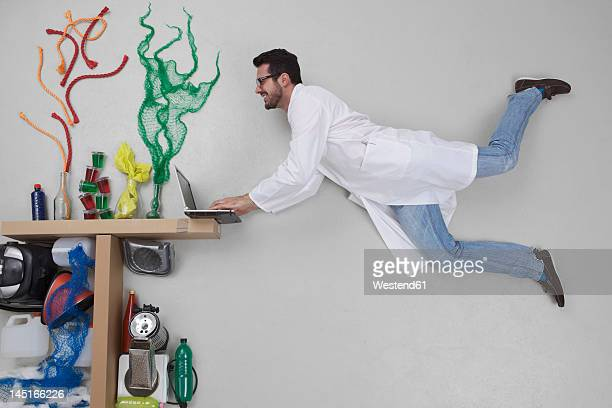 Young man doing experiment and using laptop
