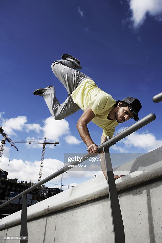 Young man doing hand stand on railing : Stock Photo