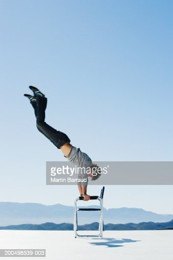 Young man doing handstand on chair, side view, outdoors : Stock Photo