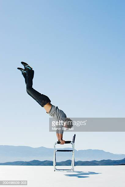 Young man doing handstand on chair, side view, outdoors