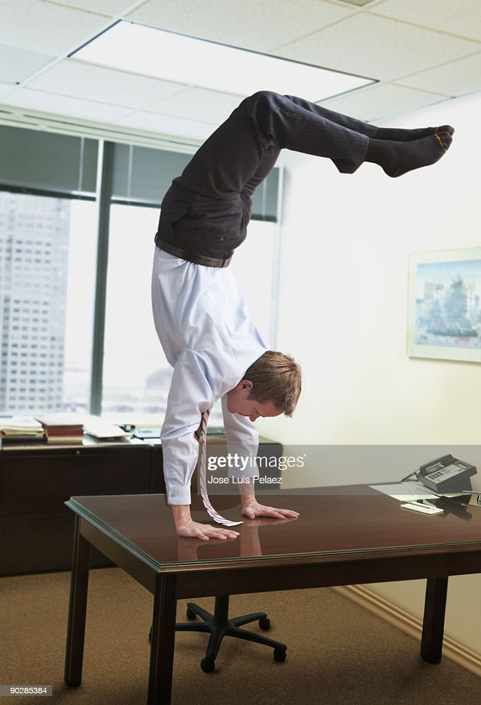 Young man doing handstand on desk : Stock Photo