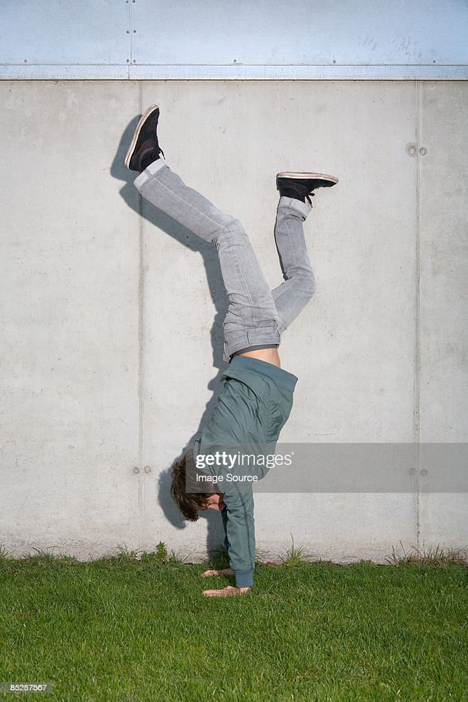 Young man doing handstand : Stock Photo