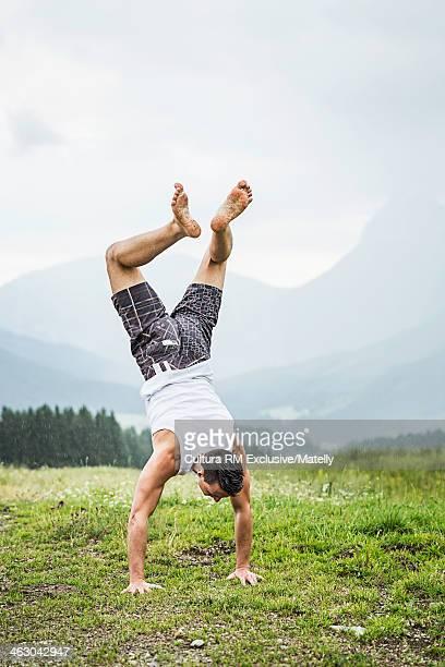 Young man doing handstand, Tyrol, Austria