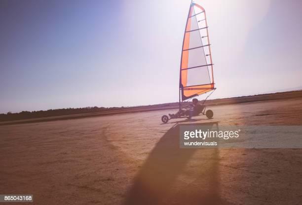 Jonge man doen land zeilen op het strand in de zomer