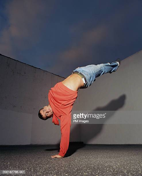 Young man doing one arm handstand