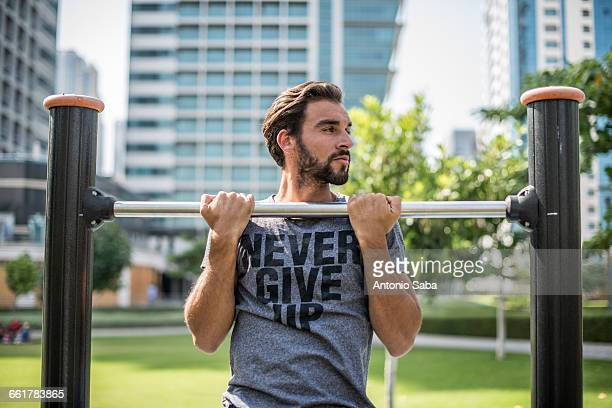 Young man doing pull ups on park exercise equipment, Dubai, United Arab Emirates