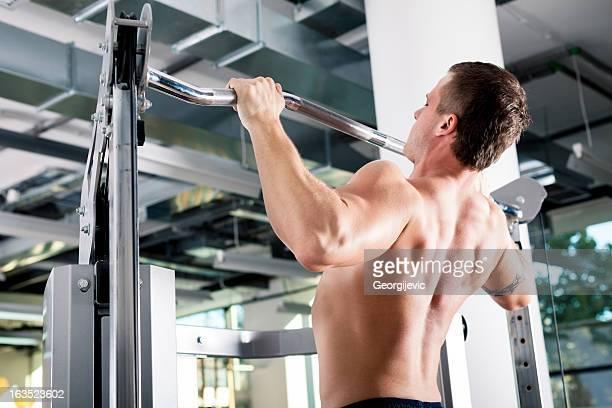 Jeune homme faire des tractions dans une salle de sport