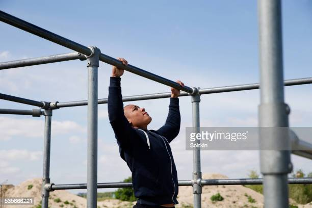 Young man doing pull-ups outside