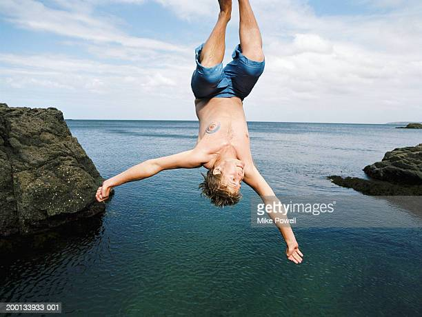 Young man doing somersault into water below