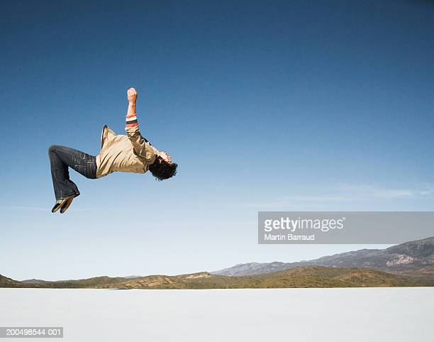 Young man doing somersault on white platform, side view