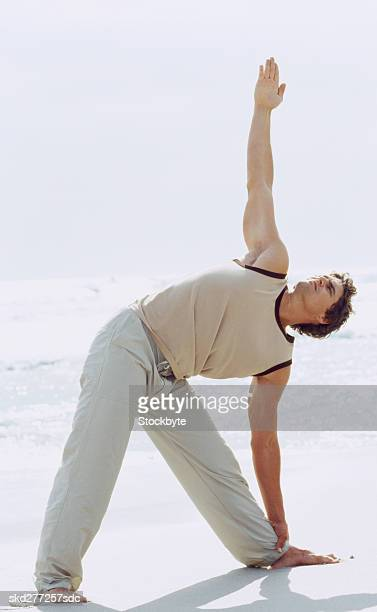 Young man doing stretching exercises on the beach