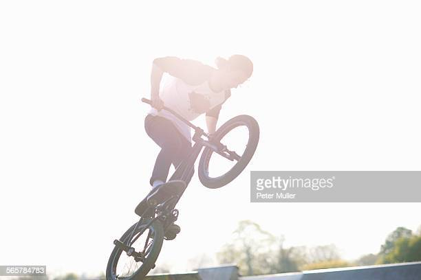 Young man doing stunt on bmx at skatepark