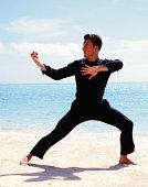 Young man doing Tai Chi on beach
