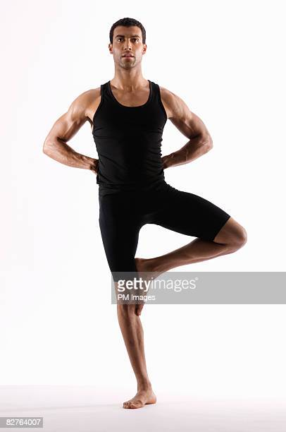 Young man doing yoga pose, standing on one foot