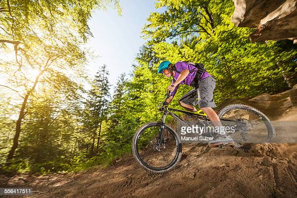Young man downhill mountain biking in forest