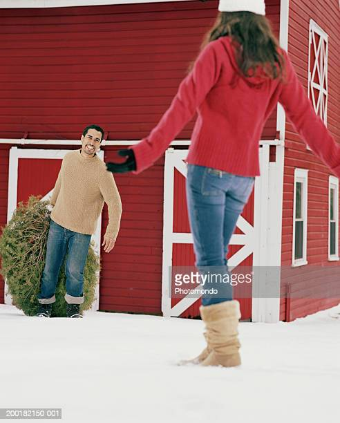 Young man dragging Christmas tree towards woman in snow