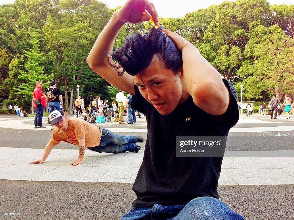 A young man dressed up in Rockabilly wear while dancing inside the square of a park in Tokyo