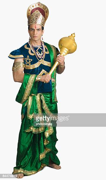 Young man dressed-up as Bhima and holding a mace