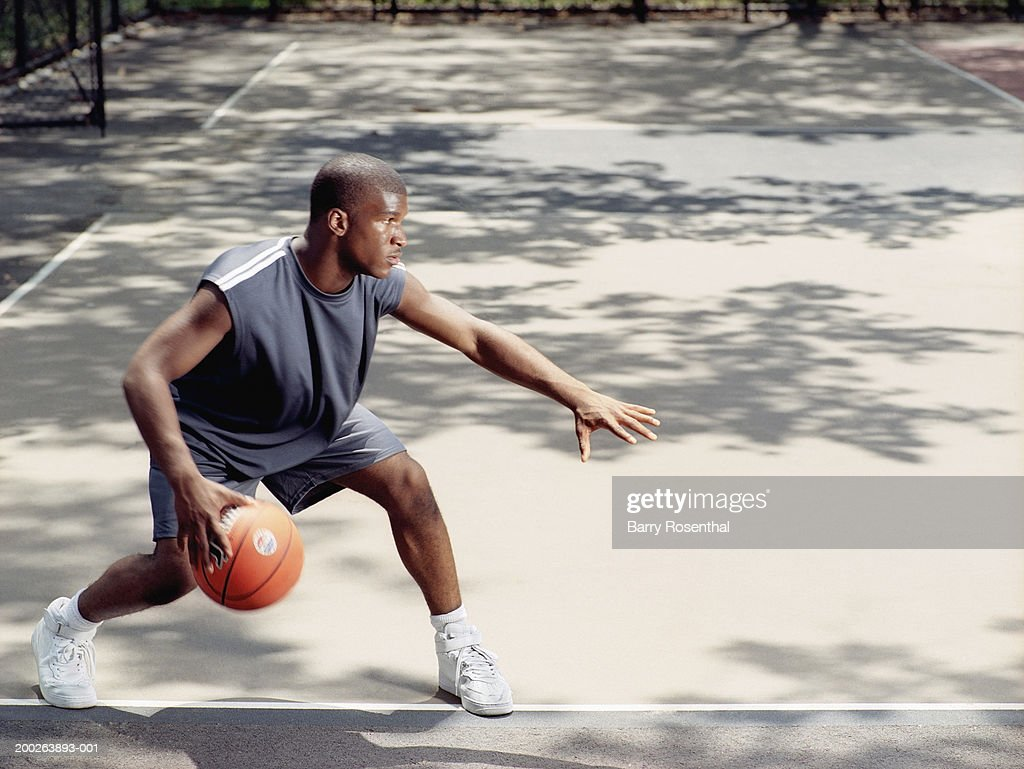 Young man dribbling basketball at outdoor court : Stock Photo