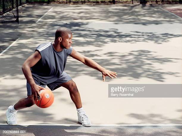 Young man dribbling basketball at outdoor court