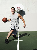 Young man dribbling basketball on outdoor basketball court