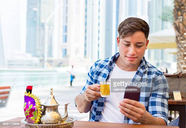 Young man drink arab tea and typing messages in Dubai