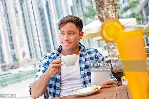 Young man drink coffee and using tablet in Dubay