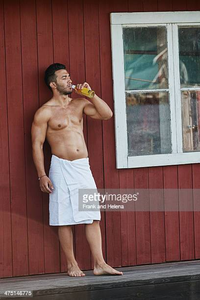 Young man drinking a beer outside sauna