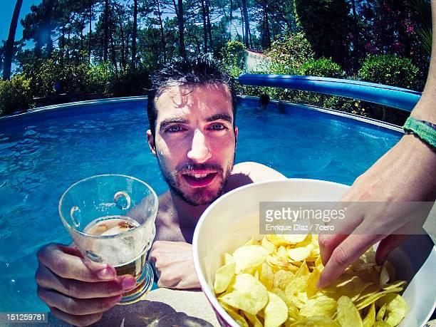 Young man drinking at pool