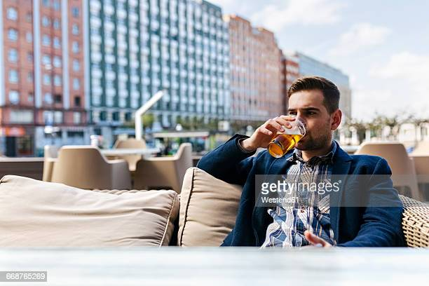 Young man drinking beer at outdoor cafe