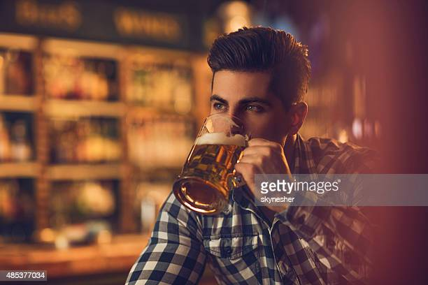 Young man drinking beer in a bar and looking away.