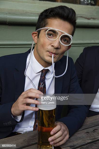 Young man drinking beer outside a London pub through a novelty straw in the shape of spectacles
