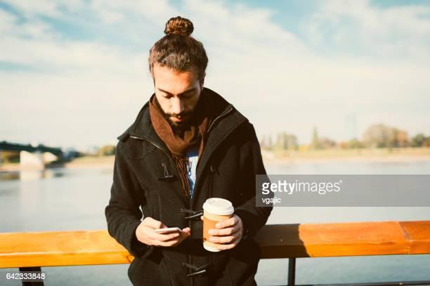 Junger Mann trinken Kaffee und mit Smart Phone auf Riverside