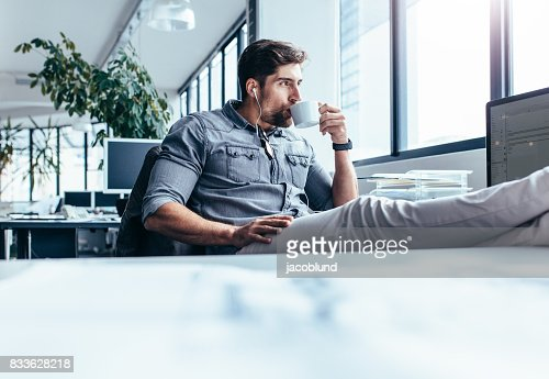 Young man drinking coffee during break in office : Stock Photo