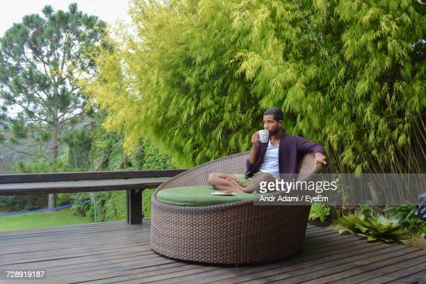 Young Man Drinking Coffee While Sitting On Lounge Chair Against Trees